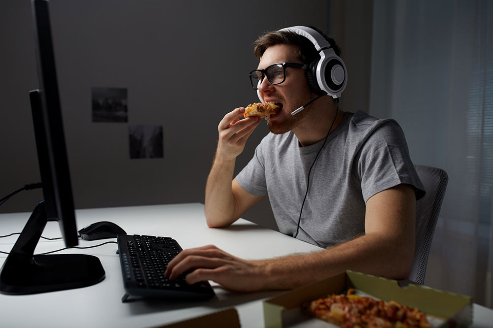 A gamer eating pizza after a successful attempt of gamer text marketing by a pizzaria.